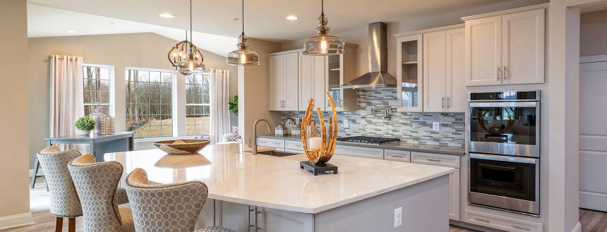 A modern kitchen with large island and bright, light-colored cabinets